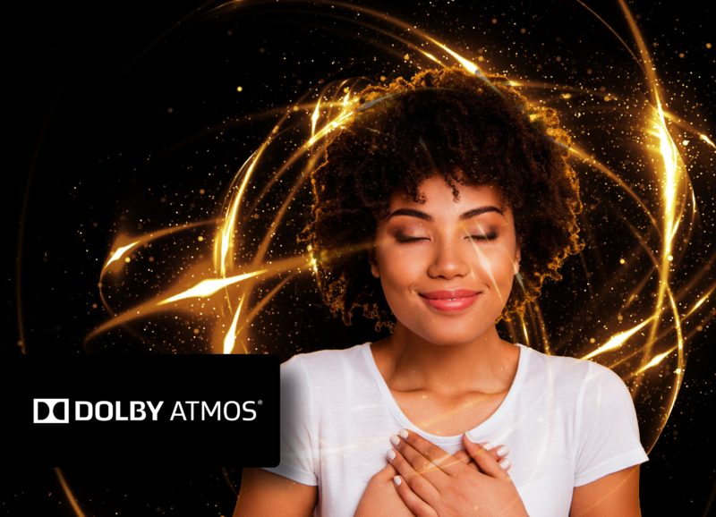 Woman with hands on her chest and Dolby Atmos label