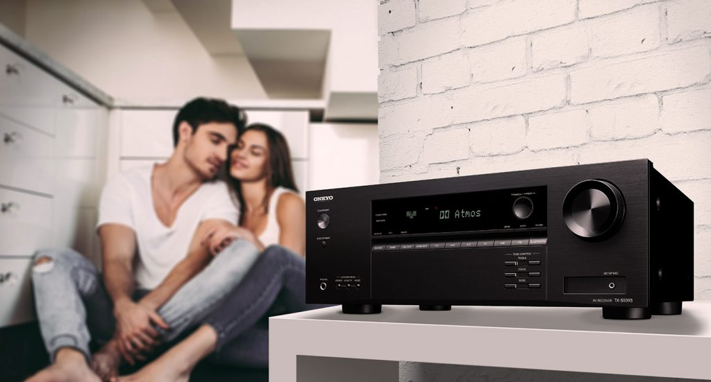 TX-SR393 AV Receiver on a shelf against a brick wall with a couple snuggling in the background