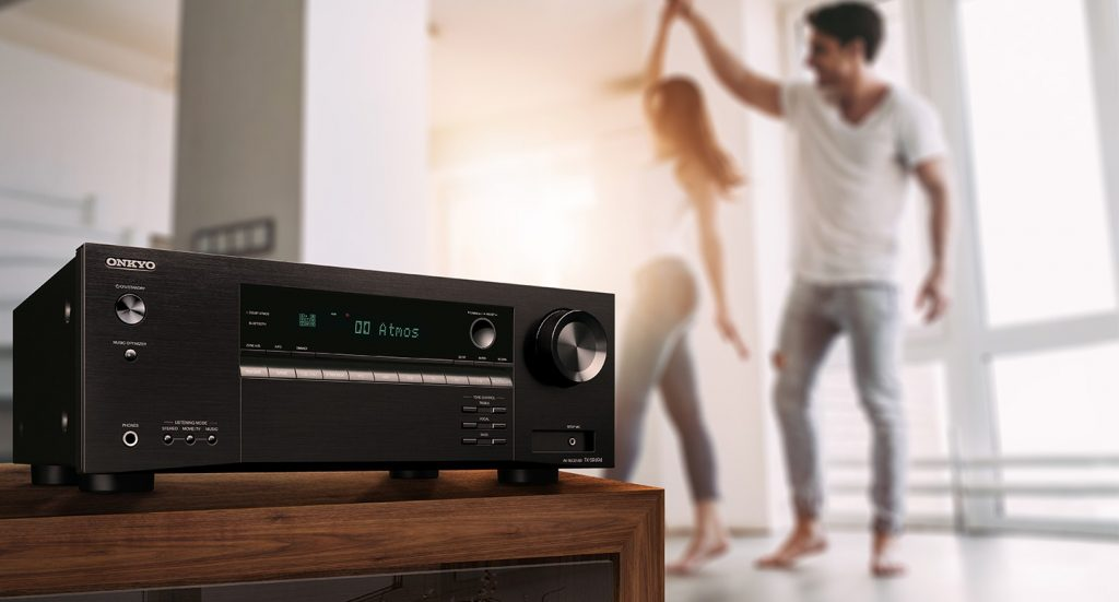 TX-SR494 AV Receiver on table with couple dancing in their living room in the background