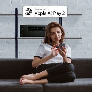 woman on couch looking at phone with av receiver on shelf works with apply airplay 2 text